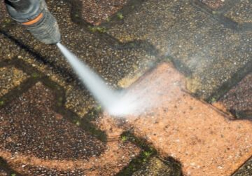 Pressure washer removing dirt from patio brick