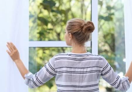 Woman looking out of a clear and bright window